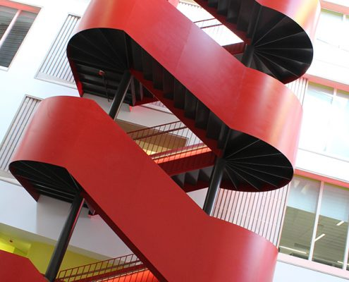 Spiral staircase with red cladding and Oak handrails to a 6th form college