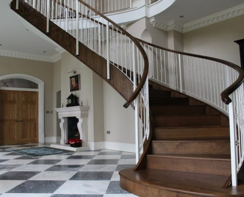 Curved staircase with bespoke Oak handrails to match stair treads complete with steel balustrade in White